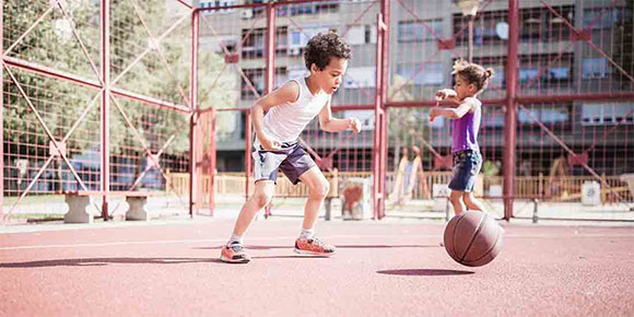 A boy and a girl play on a basketball court
