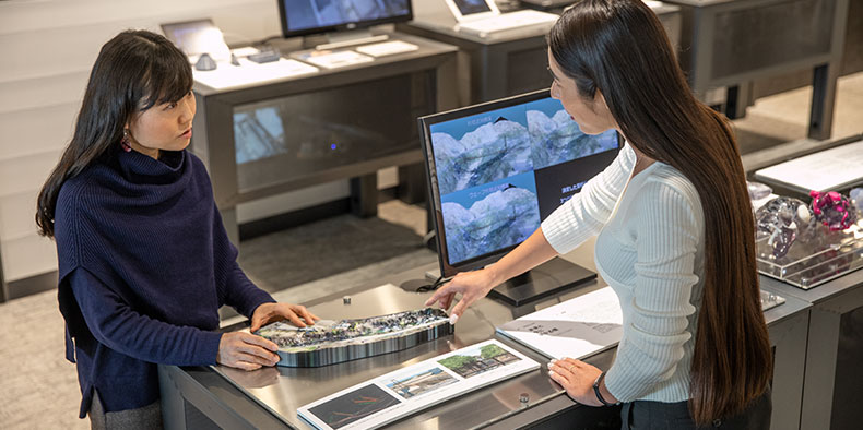 Two women working on a 3D model in an office