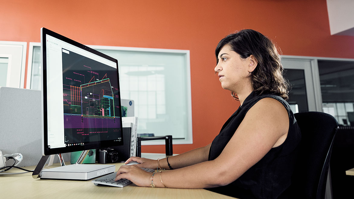 Woman using AutoCAD on a computer in an office environment