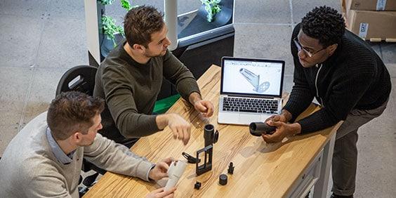 Multiethnic team of three men reviews collaborates on 3D model