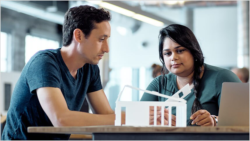 Man and woman discussing architectural model on table