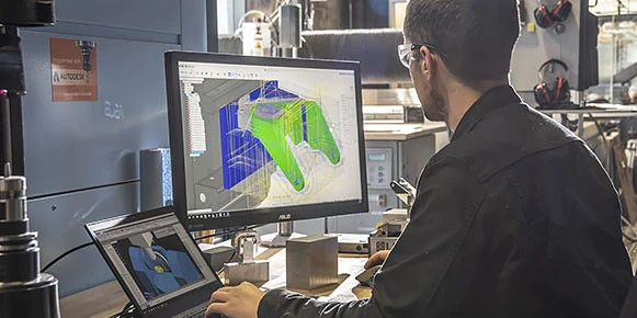 Man in workshop viewing multicolored CAD rendering on computer screen
