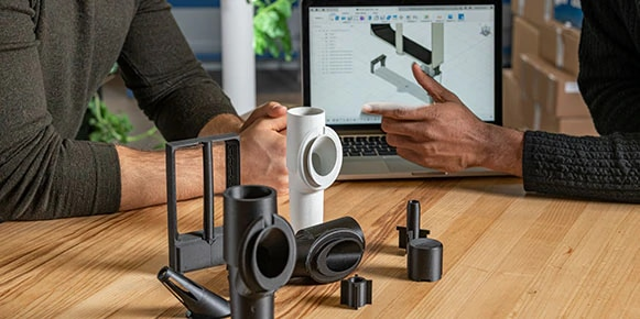 Table with black and white 3D printed parts in front of two men and a laptop with Fusion a model on the screen
