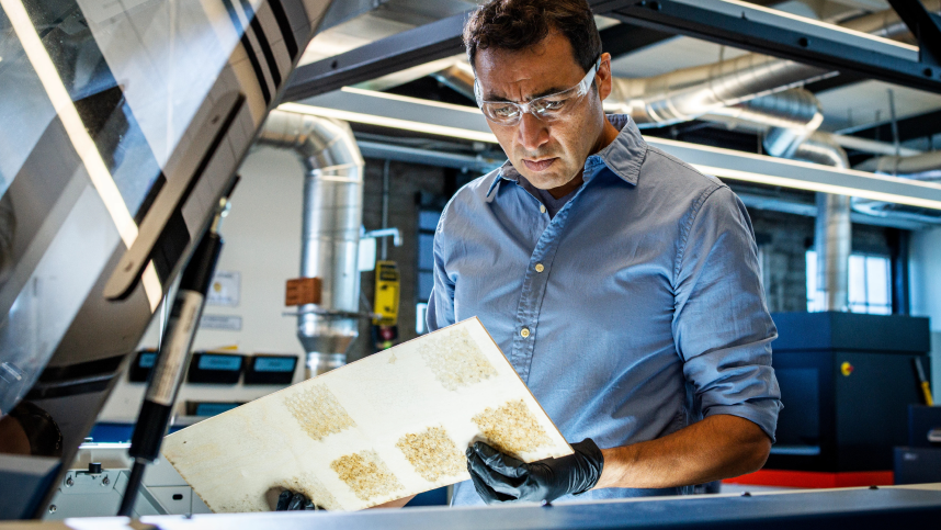 Man in blue shirt and safety glasses surrounded by ductwork, holds machined board