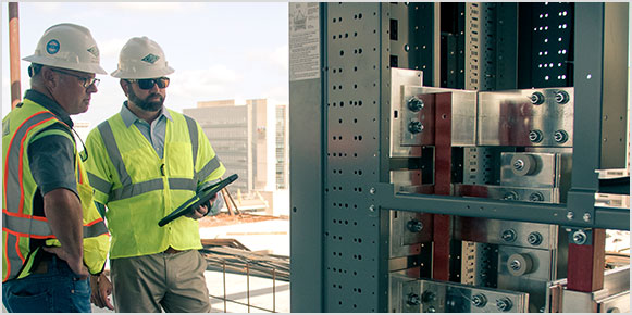Two male construction workers in hard hats and yellow vests holding a tablet and viewing an electrical panel