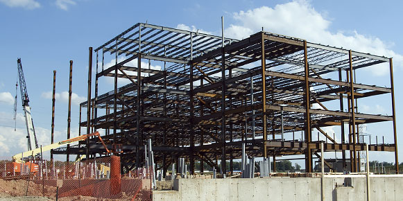 Metal frame for five-story office building and construction cranes