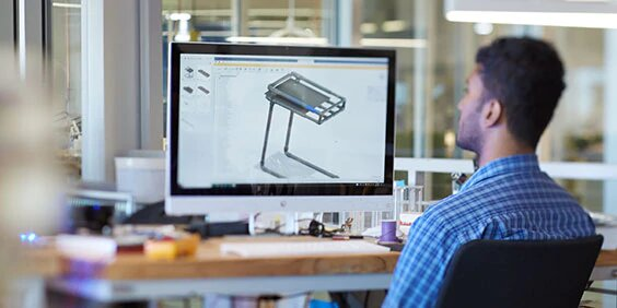 Man at desk viewing CAD image on computer screen