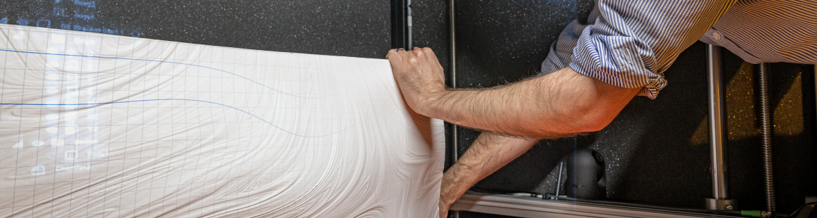 Man lifts textured white plastic sheet off table
