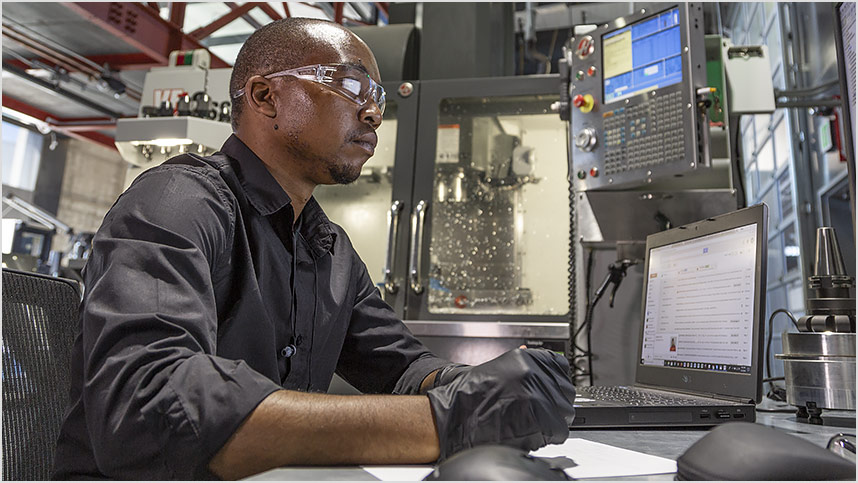Man in black shirt, safety glasses, and gloves studies a computer on a workbench