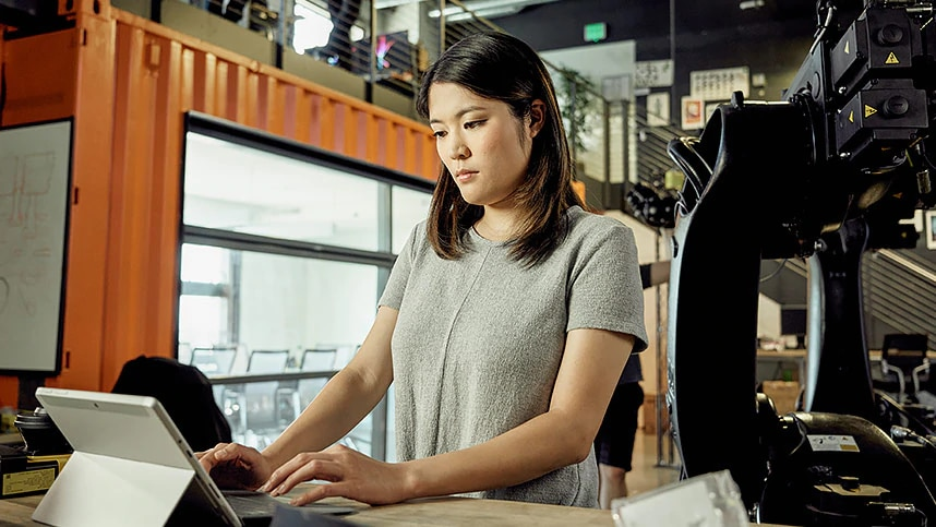 Woman in gray shirt studying computer screen